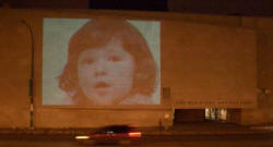 Image of a childs face projected onto the wall of The Winnipeg Art Gallery